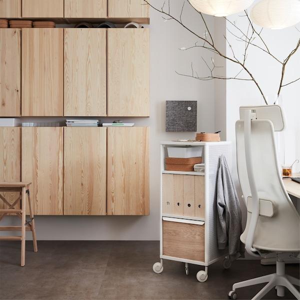 خزائن حائط IVAR من خشب الصنوبر من ايكيا، وحدة تخزين شبكية بيضاء على عجلات وكرسي دوار، في مساحة مكتبية.