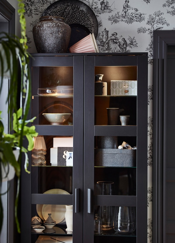 خزائن سوداء BRIMNES من ايكيا بأبواب زجاج مصنفر، لتخزين صناديق وأواني زجاجية في الداخل.