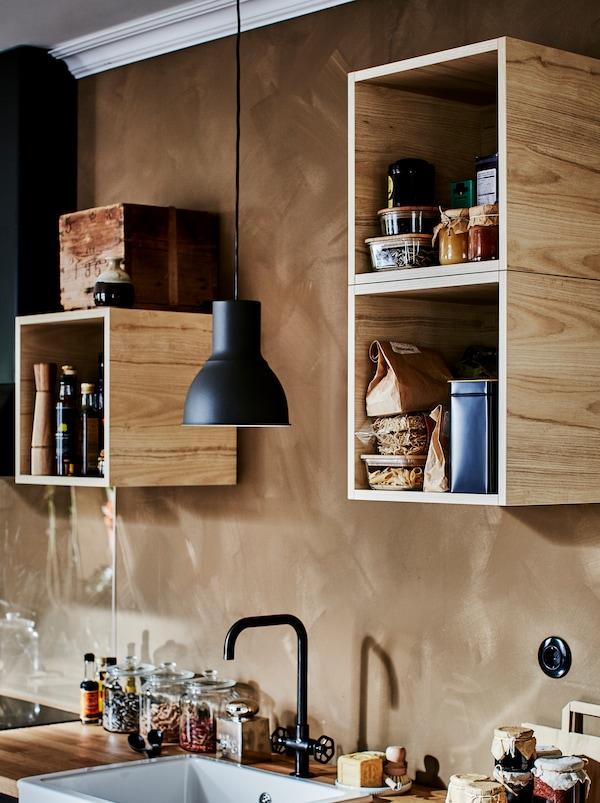 خزائن TUTEMO مليئة بإكسسوارات المطبخ المختلفة، موزعة بشكل غير متساوٍ عبر الحائط فوق مطبخ صغير.