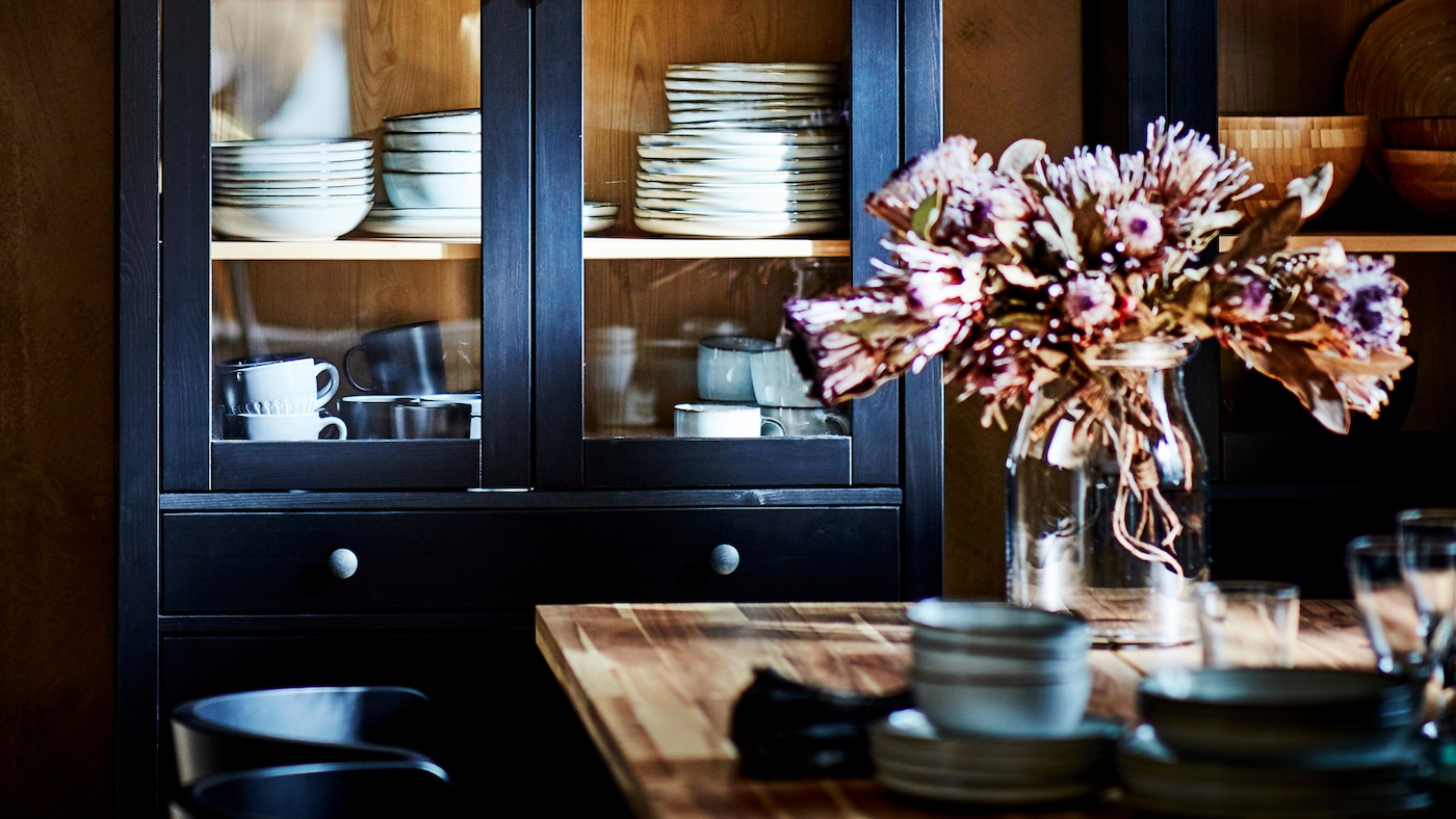 خزانة بباب زجاجيHEMNES أسود-بني مليئة بالكؤوس وأدوات المائدة، خلف طاولة عشاء مع مزهرية زهور.