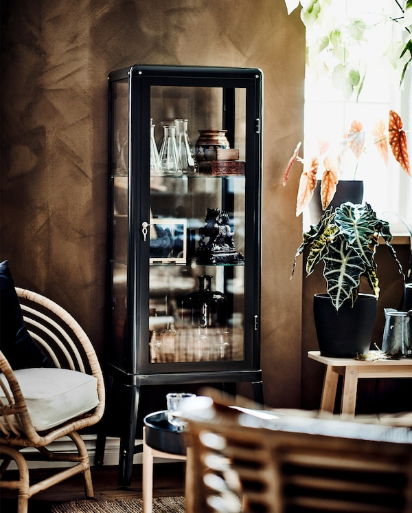 خزانة بباب زجاجي رمادي داكن بداخلها قطع زينة، نبات أخضر وكرسي بذراعين من الروطان مع وسادة بيضاء.