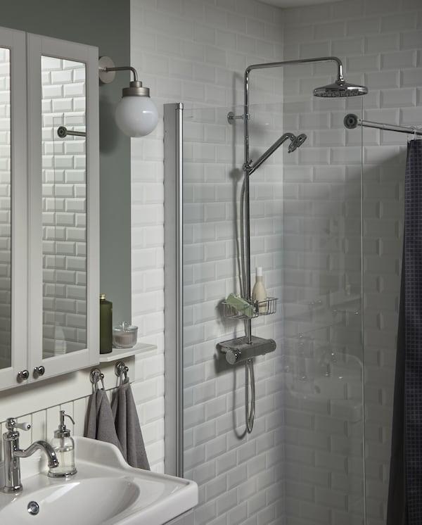 خزانة بمرآة وحوض غسل لون أبيض، ودوش ببلاطات بيضاء رأس دوش ورف دوش مطلية بالكروم.