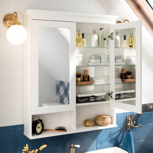 خزانة بيضاء مرآة HEMNES من ايكيا مفتوحة وبداخلها رفوف زجاجية، ومرايا على جانبي الباب وإكسسوارات حمام.