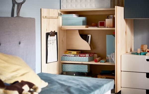 خزانة IVAR مفتوحة منظمة بداخلها ألعاب في صناديق وحافظات مجلات.