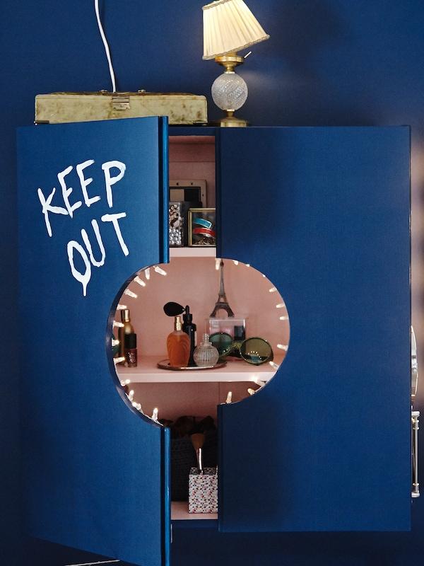 خزانةIVAR مطلية بالأزرق مفتوحة قليلًا لتكشف رفوف وظهر لون وردي، مليئة بمنتجات وإكسسوارات التجميل.