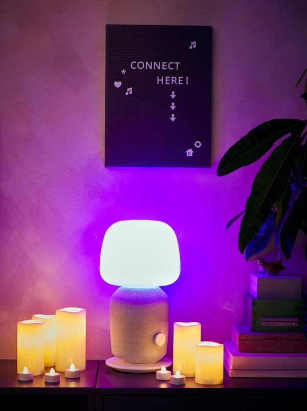 خزانة جانبية عليها مصباح SYMFONISK مضاء مع سماعات واي فاي، وشموع كتلة وشموع صغيرة LED حوله، ولوح تعليق SVENSÅS من أعلى.