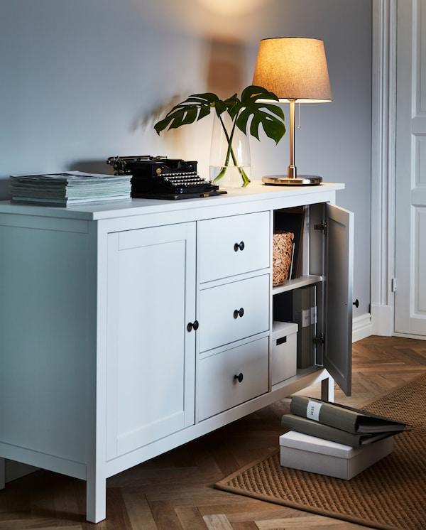 خزانة جانبية HEMNES مع مصباح والعديد من القطع الفنية في الأعلى. يكشف الباب الموارب عن صناديق ومجلدات مخزنة بداخلها.