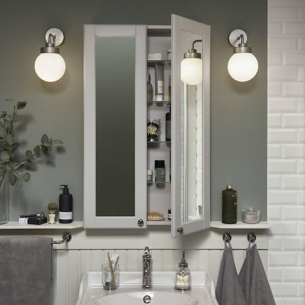 خزانة مرآة مرتفعة ورفيعة فوق حوض غسل أبيض. أحد الأبواب مفتوح وبداخلها منتجات تجميل مخزنة.