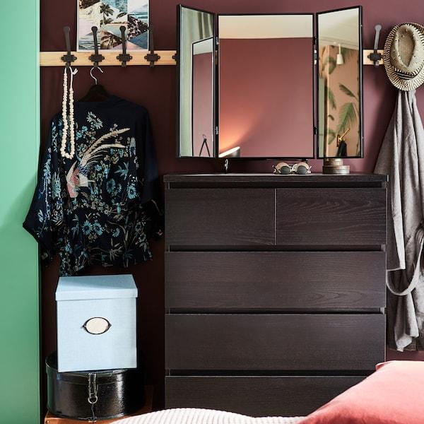 خزانة ذات أدراج بلون أسود-بني، ومرآة سوداء، ورفوف من خشب الصنوبر مع خطافات رمادية وصندوق تخزين أزرق مع غطاء.