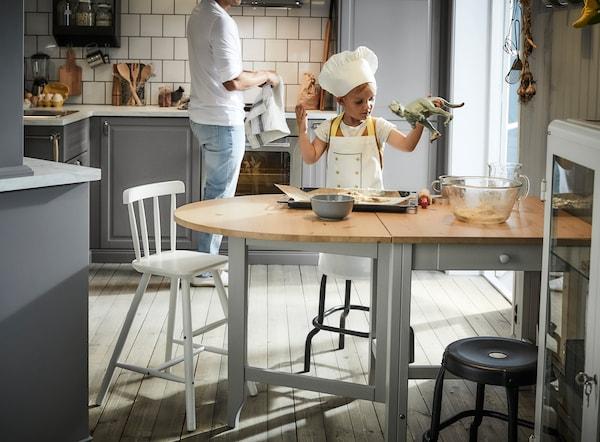 Kid preparing baking dough on GAMLEBY dinning table.