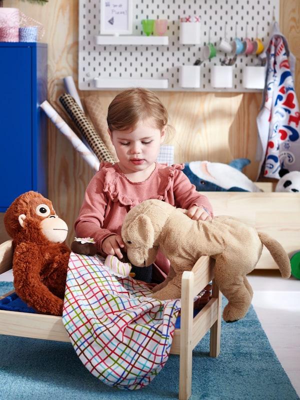 Kids chemical free toys showing child with the DJUGELSKOG Orangutan and GOSIG GOLDEN plush dog
