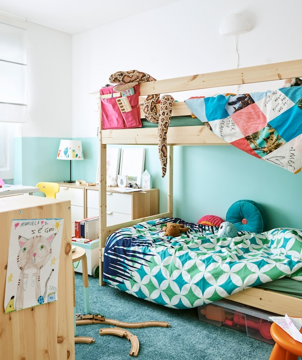 Kids' room with a white and turquoise scheme, wood bunk bed with colourful bedding, wood and white drawers and turquoise rug.