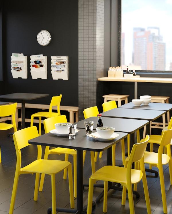 Kilka dostawionych do siebie stołów STENSELE z żółtymi krzesłami JANINGE, ustawione w stołówce. Na jednym ze stołów stoją białe talerze i szklanki z wodą.