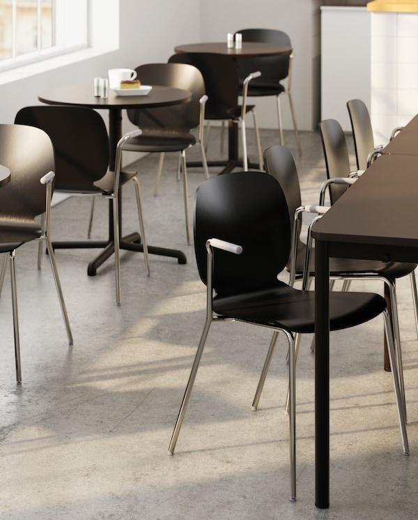 Kilka dużych stołów z dopasowanymi kolorystycznie krzesłami. Obok, pod oknem, stoi kilka małych, okrągłych stolików z krzesłami. Na jednym z nich stoi biały kubek.