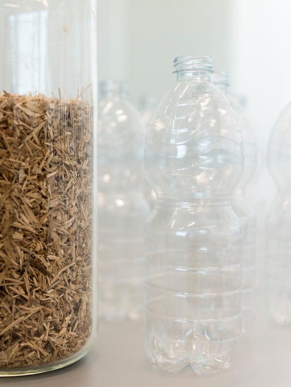 Kilka pustych plastikowych butelek ustawionych obok szklanego pojemnika wypełnionego trocinami.
