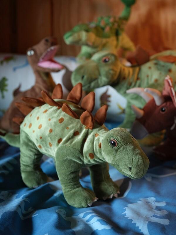 Kilka różnych pluszowych dinozaurów z serii JÄTTELIK zgromadzonych na kołdrze w dinozaury.