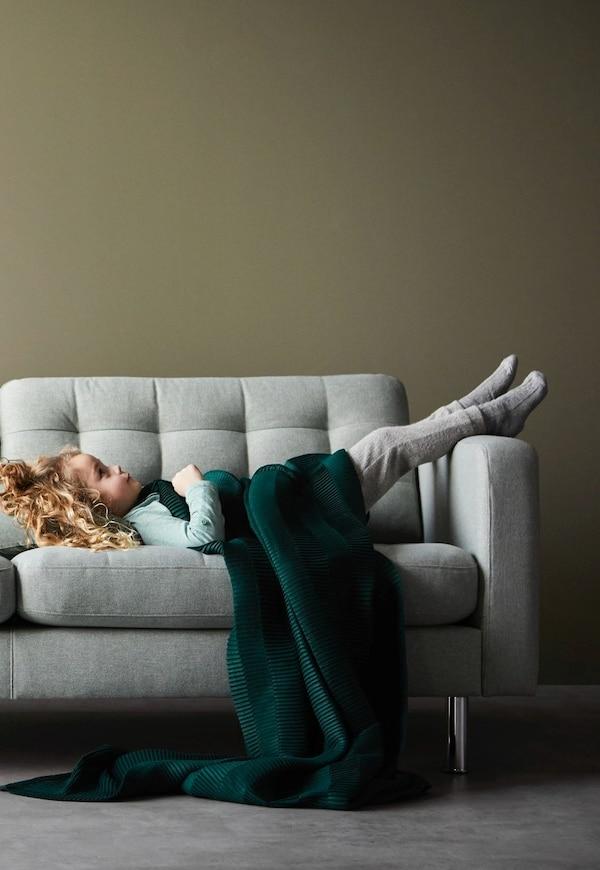 Kind auf LANDSKRONA Couch mit grüner Decke