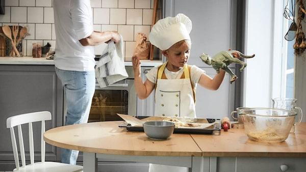Kind mit Schürze steht in der Küche und backt mit einem Erwachsenen
