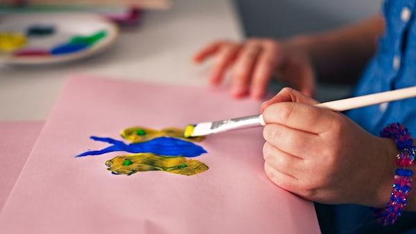 Kind zeichnet einen Schmetterling