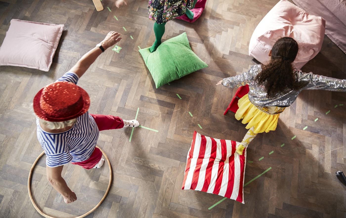 Kinder und Erwachsene spielen auf dem Fussboden ein Spiel mit Kissen.