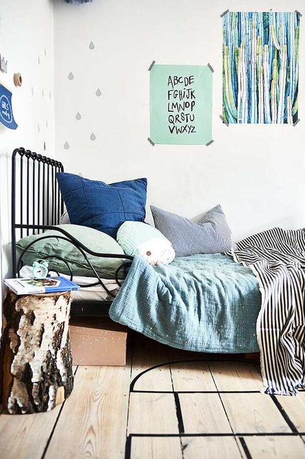 kinderbed zwarte spijlen bedekt met kussens en posters aan de muur