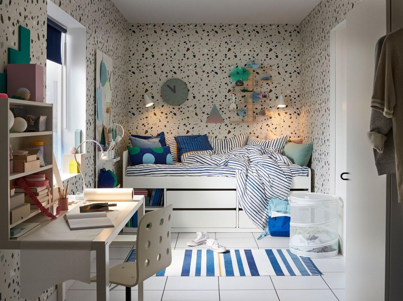 Kinderzimmer in blau mit weißem Bett mit Schubladen, Schreibtisch, blau-weißem Teppich & blauen Kissen.