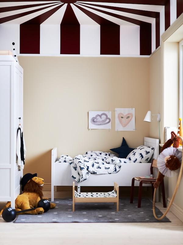 Kinderzimmer mit einem SUNDVIK ausziehbarem Bett, Spielzeug und einer Zimmerdecke, die wie das Dach eines Zirkuszeltes gestrichen ist.