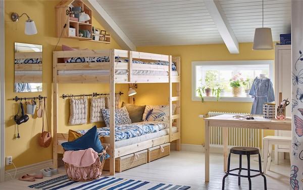 Kinderzimmer mit gelben Wänden, Etagenbettgestell aus Holz, blau-weißen Accessoires & Holztisch.
