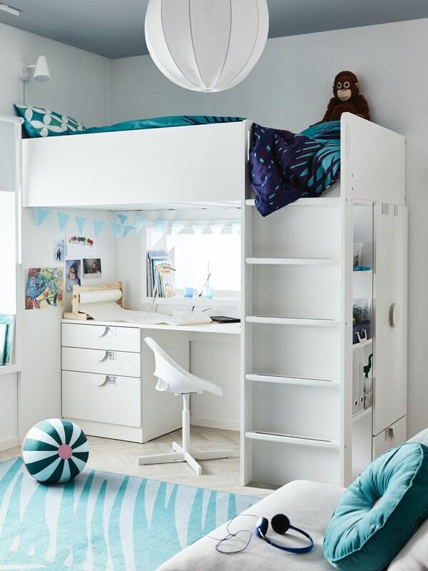 Kinderzimmer mit weißem Hochbett und einem Schreibtisch unterhalb. Das Zimmer ist mit einem Teppich, Bettwäsche und Kissen in blau geschmückt.