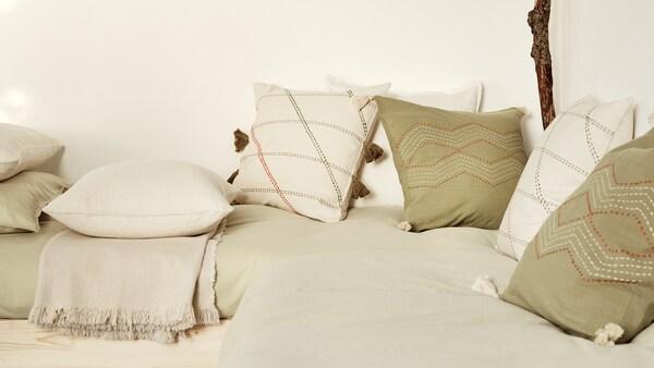 kirjailtuja luonnonvalkoisia ja vihreitä HERVOR- ja HALLVI-tyynyjä vaalean sohvan päällä.