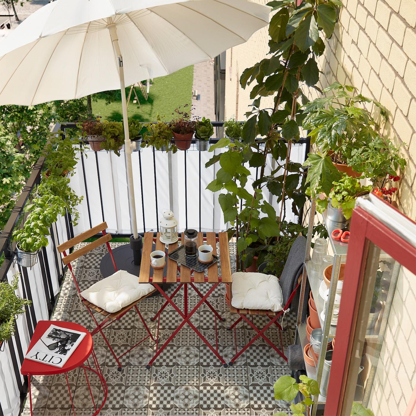 Kis erkély, sok fűszernövénnyel és növénnyel, piros ülőke, fehér napernyő és két szék, összecsukható asztal.