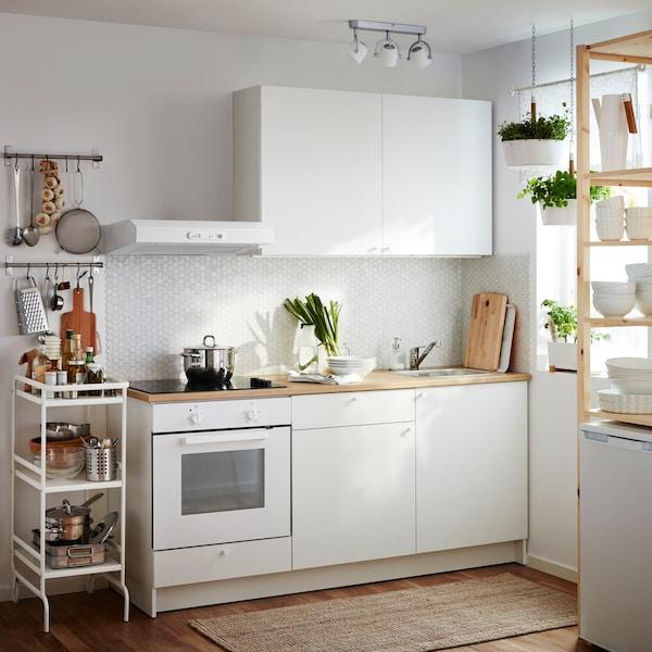 Kis fehér konyha, teljes alsószekrénnyel, ajtókkal, fiókokkal, munkalappal és faliszekrényekkel. Fehér fali páraelszívó, sütő és fekete üvegkerámia főzőlap.