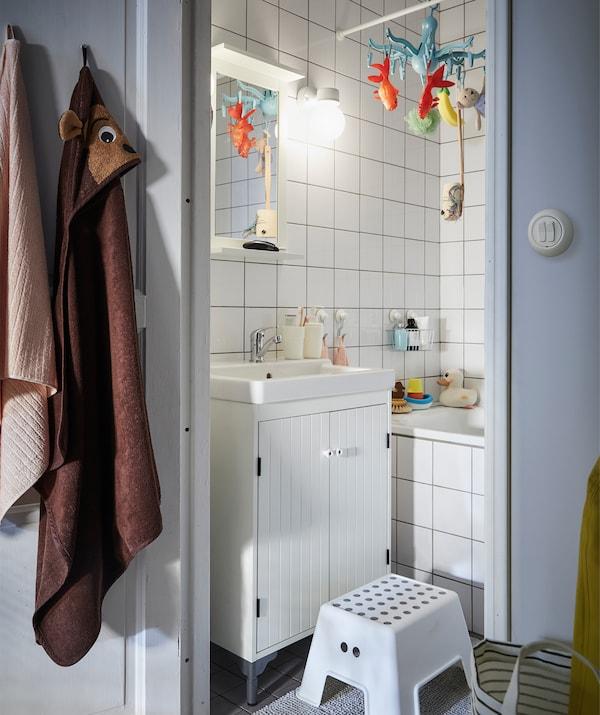 Kis fürdőszoba, fehér csempével és egy ülőke.