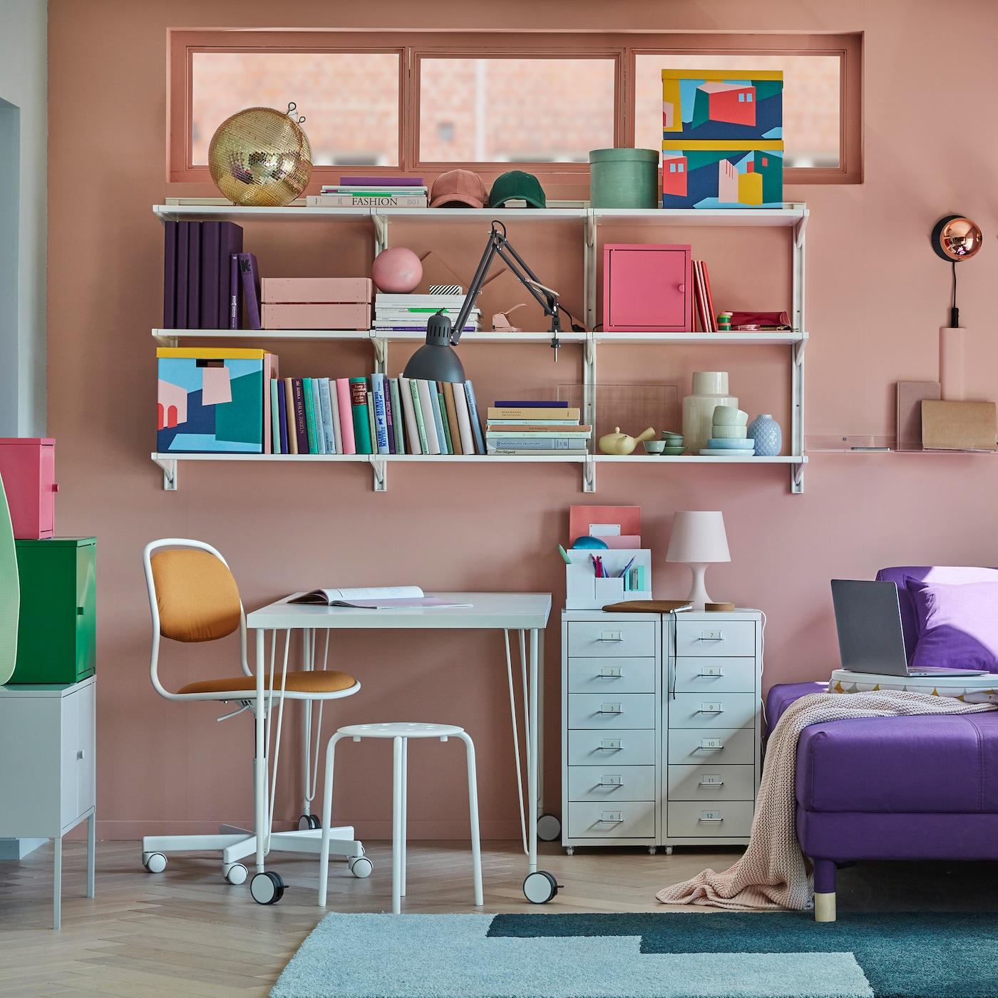 Kis otthoni iroda LINNMON/KRILLE asztallal, fehér színben, görgős lábakkal, polcok, tárolószekrények és kanapéágy.