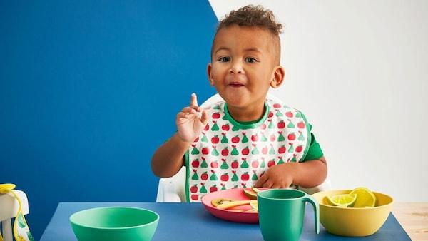 Kisbaba eszik egy asztalnál, kék, zöld, sárga és piros IKEA HEROISK terítékkel, PLA műanyagból.