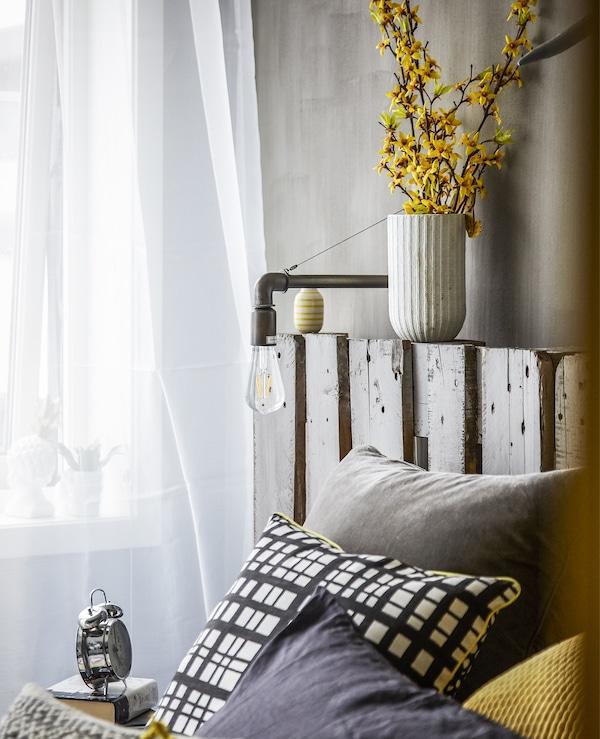 Kissen auf einem Bett, u. a. mit LUNNOM LED-Lampe E27 400 lm tropfenförmig Klarglas.
