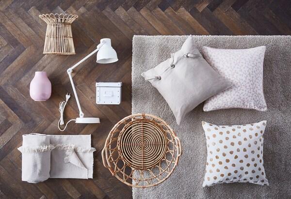Kissen, Holzkörbe, Leselampe, & Box in hellen Pastelltönen auf einem Holzboden & grauen Teppich