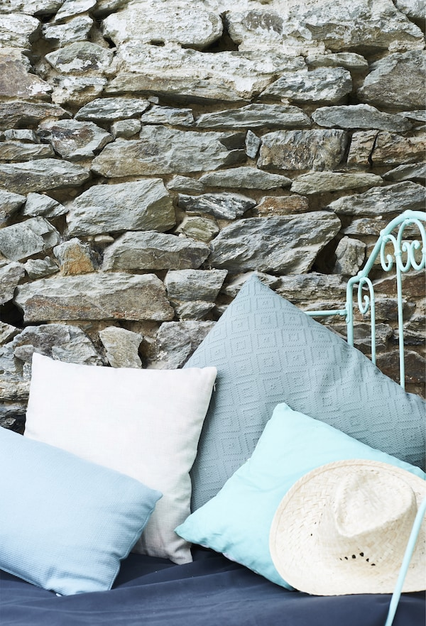 Kissen in verschiedenen Blautönen vor einer alten Mauer, u. a. mit DITTE Meterware dunkelblau.
