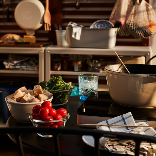 Kit pentru fondue pe un set cu masă rotundă mică pentru două persoane pe un balcon, cu o frântură de bucătărie pe fundal.