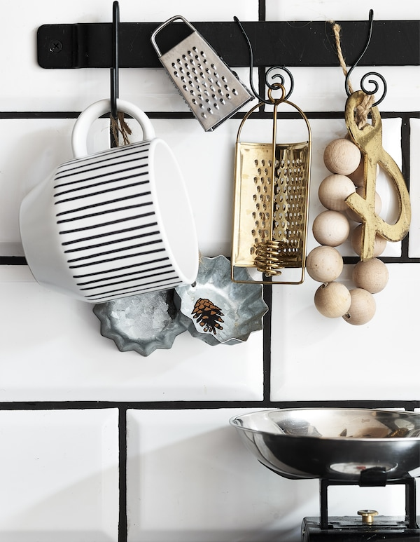 Kitchen accessories hanging on a black rail on white tiles.