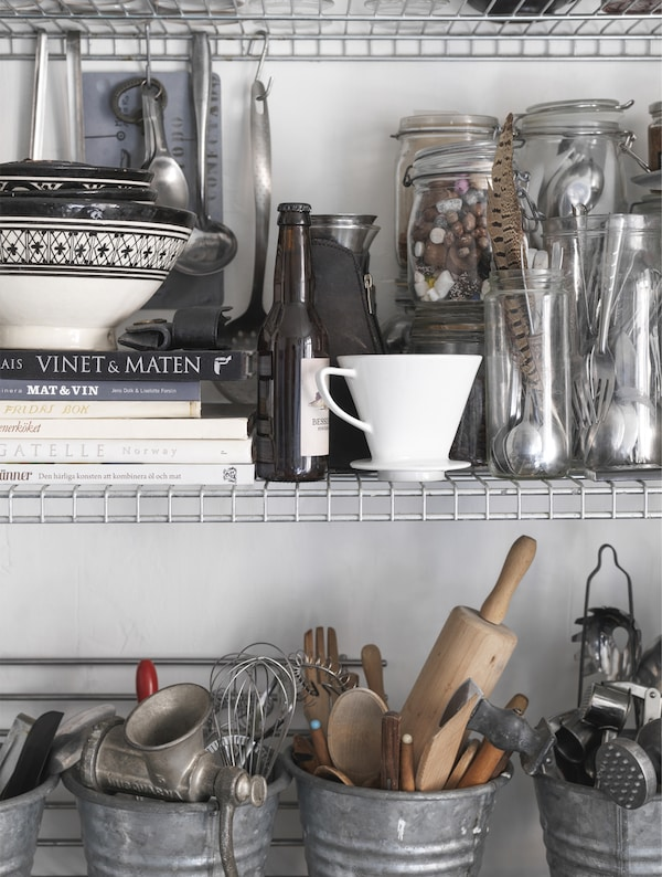 Kitchen accessories stored in jars and buckets.