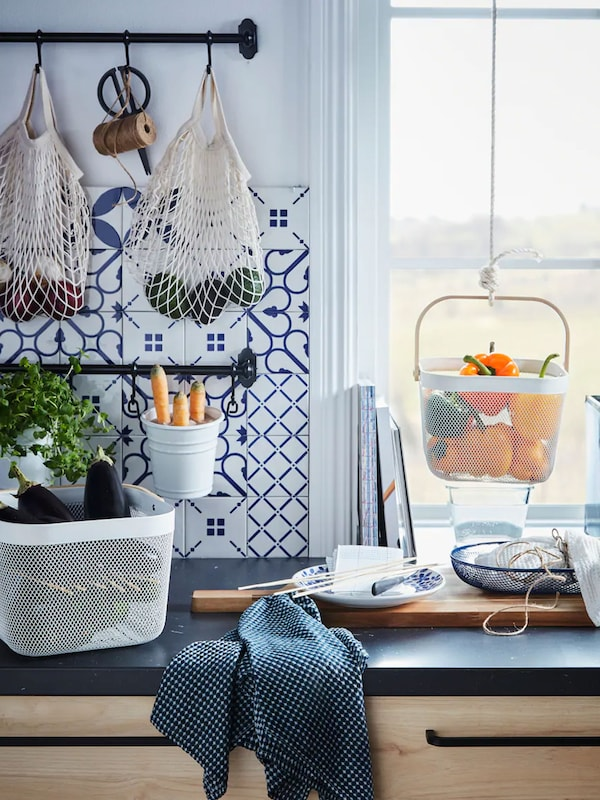 Kitchen counter with baskets of fresh vegetables