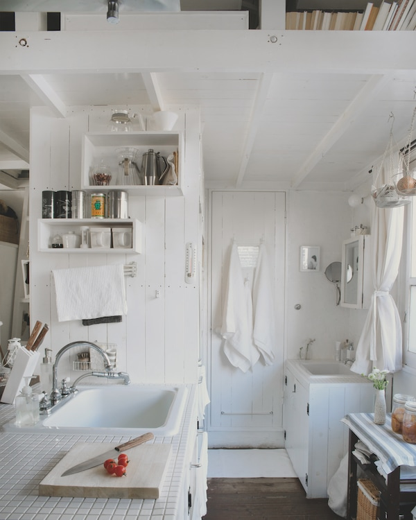 Kitchen storage and a tidy bathroom sink area in a small, white, Tokyo home.