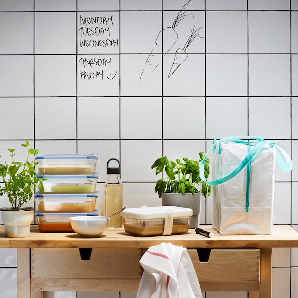 Kitchen table with four stacked food containers and a lunch bag.
