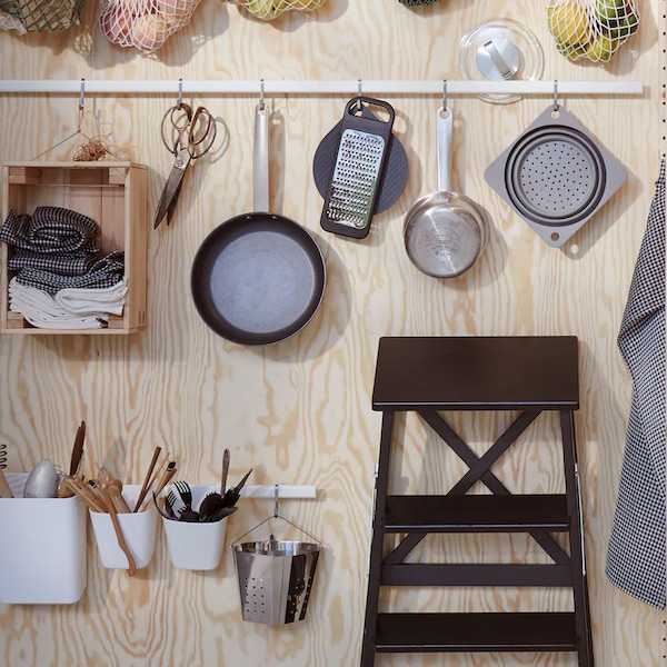 Kitchen utensils and food bags hang from white, SUNNERSTA rails fixed to a plywood wall next to a black, BECKVÄM step stool.