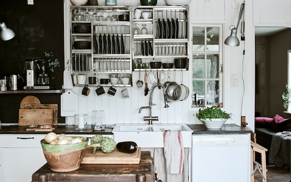 Kitchen wall with white-washed wood panelling and blackboard paint, plus industrial style open shelves full of crockery.