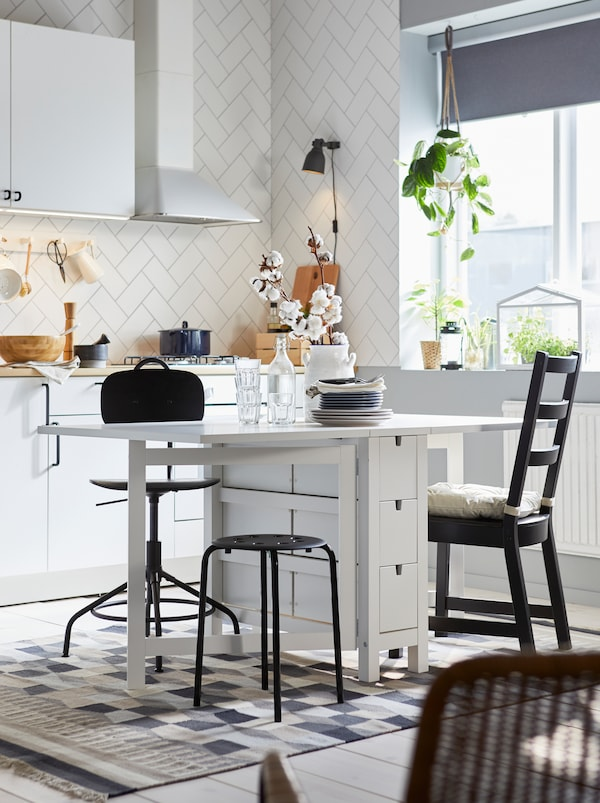 Kitchen where a white NORDEN gateleg table, both leafs out, is surrounded by odd seating, including a KULLABERG chair.