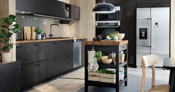 Kitchen with black cabinets and an island with shelves holding food and dishes