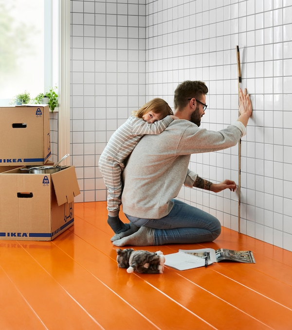Kitchen with boxes and a man measuring the tiled kitchen wall, while a small child hugs him from behind.