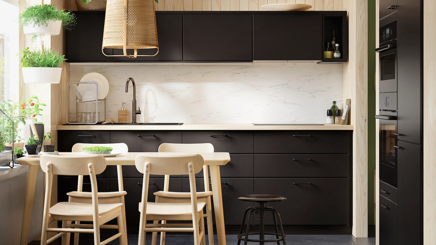 Kitchen with dark fronts and a dining table and chairs in light wood.